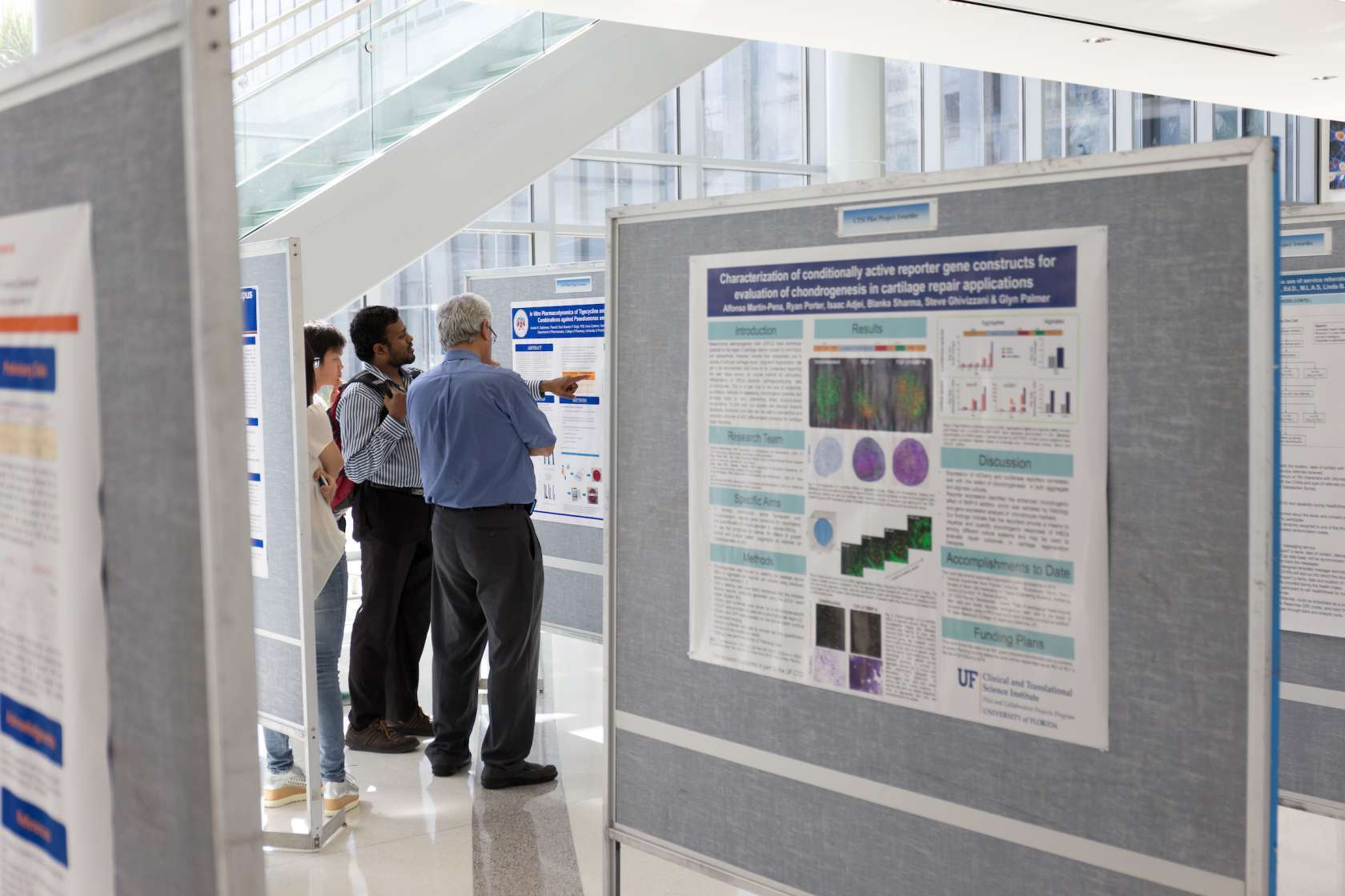 three people standing in front of research poster